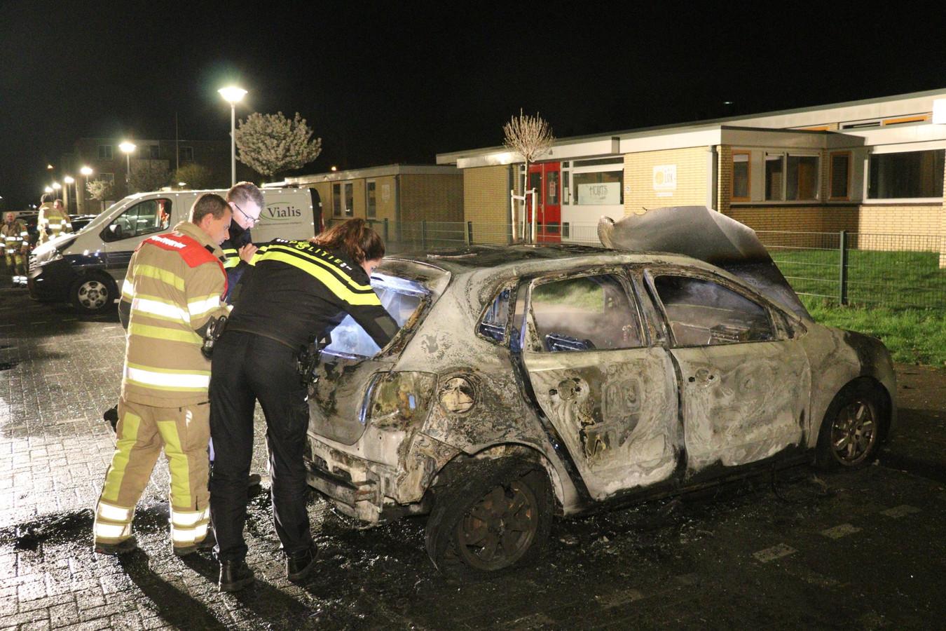 Autobrand in de Utrechtse wijk Zuilen, waarbij agenten onderzoek doen nadat de brandweer heeft geblust.