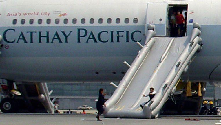 De passagiers verlaten het vliegtuig na de noodlanding via 'glijbanen'.
