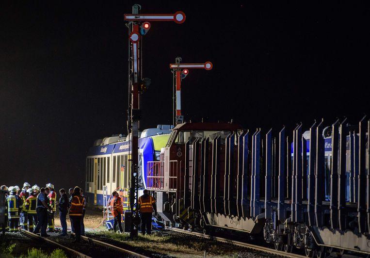 Brandweermannen en reddingswerkers zijn aan het werk bij de gecrashte treinen.