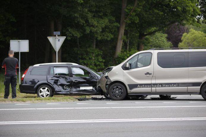 De situatie vlak na het ongeluk nadat het busje vol in de zijkant is geknald van de zwarte personenauto.