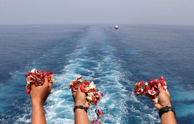 Nabestaanden van passagiers en bemanningsleden strooien bloemblaadjes op de plek waar Lion Air vlucht JT610  in zee stortte.   Beeld Reuters
