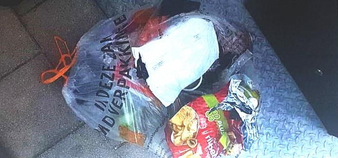 Een foto die Kamperman ontving bij de brief van de gemeente, waarop de zak plastic afval met de daarin aangetroffen zak chips te zien is.
