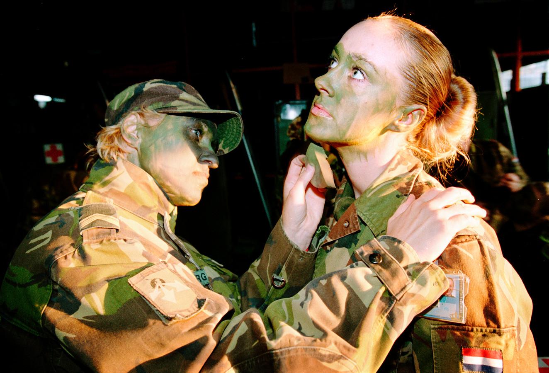 Militairen schminken elkaar met camouflage-schmink in Ermelo.