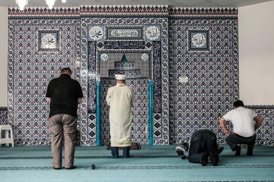 Mannen bidden in de gebedsruimte. Foto: Jan Ruland van den Brink