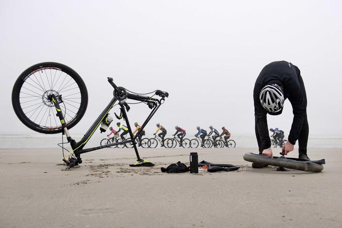 Een pechvogel onderneemt rigoureus actie bij een lekke band tijdens de Egmond-Pier-Egmond strandrace voor fietsers in Noord-Holland. Foto Olaf Kraak