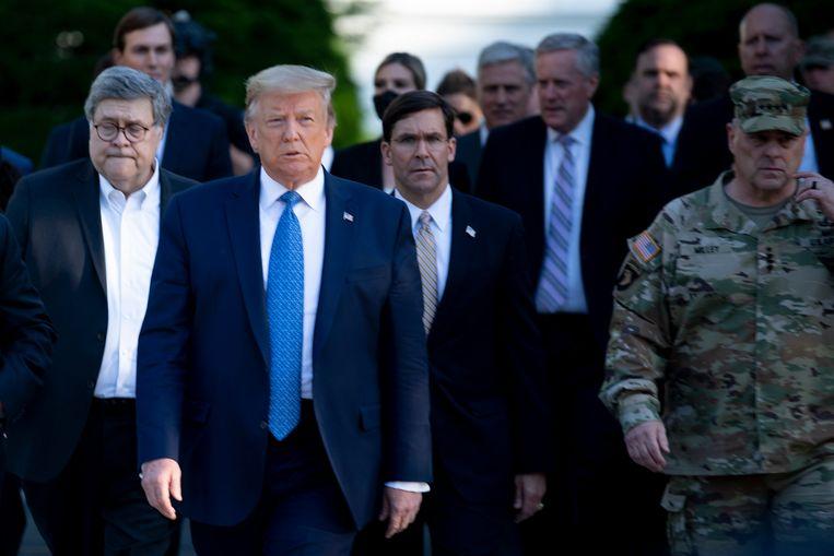 President Donald Trump loopt met zijn ministers van justitie en defensie, William Barr en Mark T. Esper naar een kerk in Washington. Rechts opperbevelhebber Mark A. Milley.  Beeld AFP
