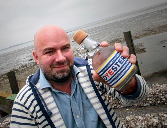 Chris Liebau met zijn  oesterwodka aan de oever van de Oosterschelde.  Foto: Gerard van Offeren/Pix4Profs