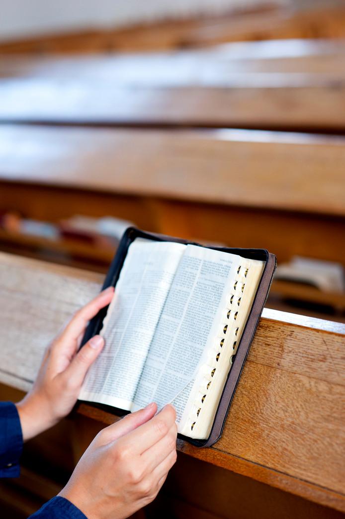 Een kerkganger leest in een protestante bijbel.