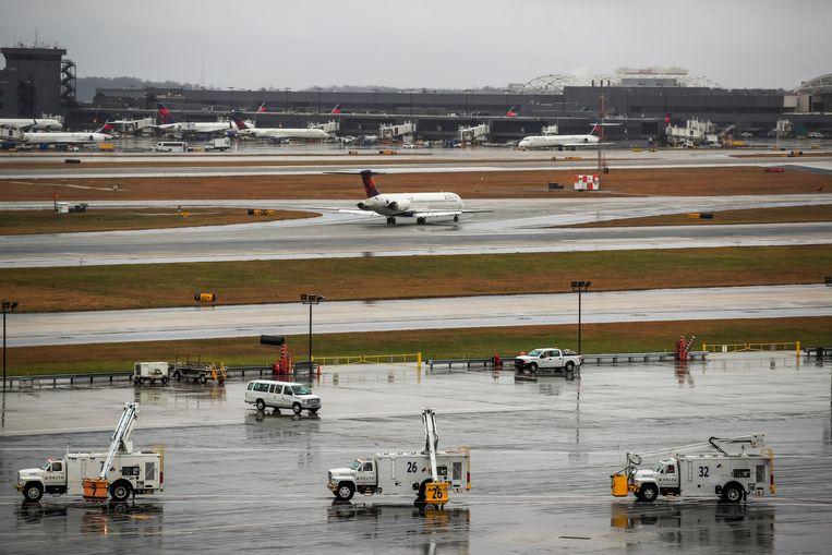 Een vliegtuig van Delta Airlines is zojuist geland in Atlanta in de Amerikaanse staat Georgia, terwijl vrachtwagens met anti-vries klaarstaan om de vleugels van vertrekkende vliegtuigen te ontdooien.