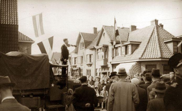 Dominee Uitenhuis spreekt in Borculo vanaf een legervoertuig de menigte toe.