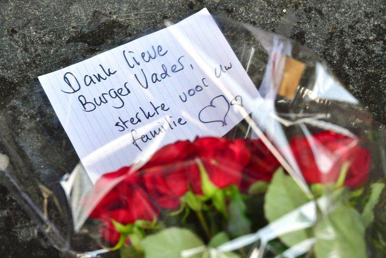Mensen laten bloemen achter bij de ambtswoning. Beeld anp