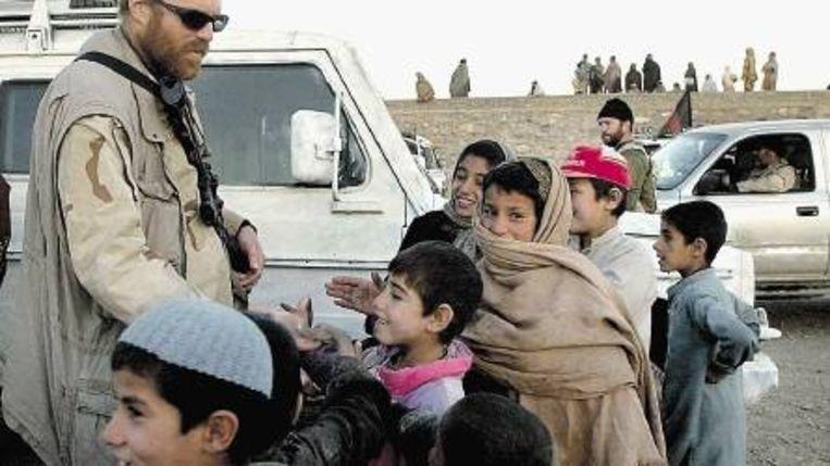Een Amerikaanse soldaat in Kandahar tijdens een verbroederende ontmoeting met Afghaanse kinderen. ( (FOTO EPA) Beeld