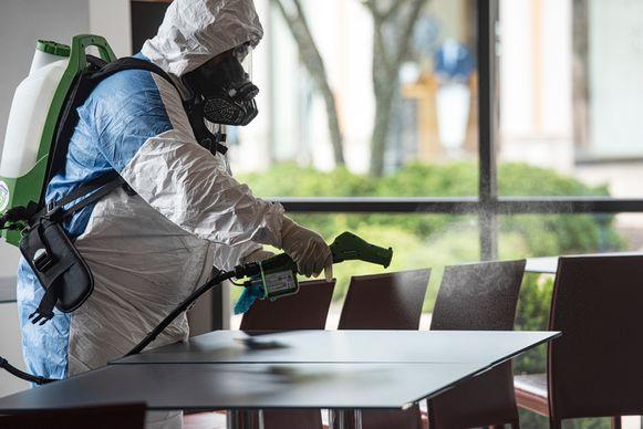 Een gezondheidswerker ontsmet een tafel.