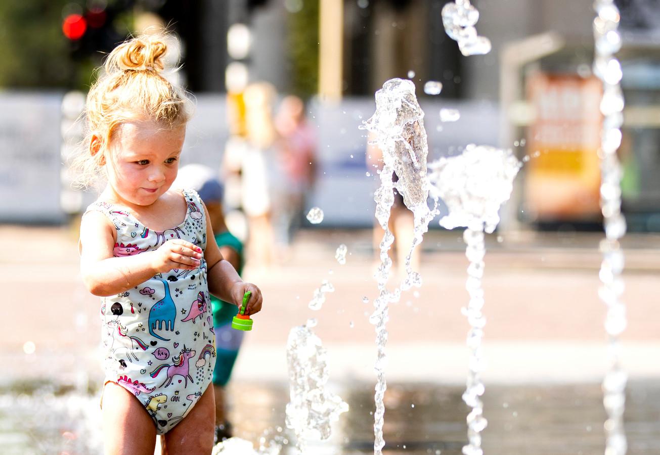 Een meisje speelt in een fontein op het Haarlemmerplein in Amsterdam.
