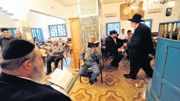 Joodse mannen bidden in een synagoge in Asjen in Noord-Marokko. Beeld afp