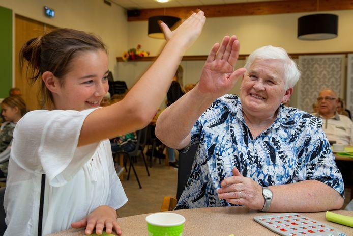 Een scholiere van de Mariaschool en een bewoonster van Sint-Elisabeth spelen samen bingo.