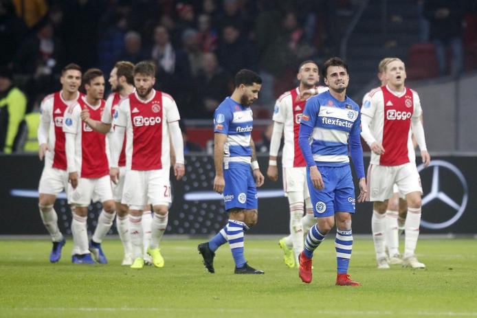 Spelers van Ajax zijn blij na een doelpunt, de spelers van De Graafschap treuren.