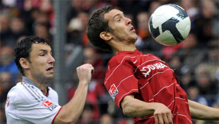 Julian Schuster van Freiburg (r) controleert de bal voor Mark van Bommel. Louis van Gaal heeft zaterdag met Bayern München een belangrijke overwinning behaald in de Duitse voetbalcompetitie. Foto EPA Beeld