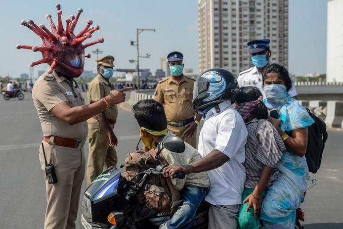 Een politieagent met 'coronahelm' in Chennai (India) spreekt een gezin toe . India is in lockdown.