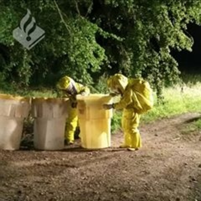 De brandweer heeft de gedumpte vaten met xtc-afval opgeruimd met beschermende pakken aan. De blauwe en witte gedumpte vaten worden veilig afgevoerd in de gele containers.
