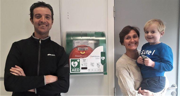 De uitbaters van TC De Bergen in Herenthout bij de defibrillator die in de tennisclub een plaatsje kreeg