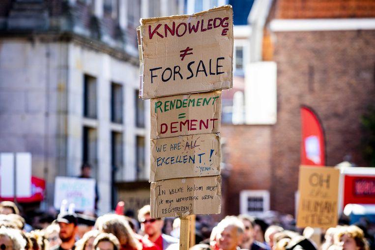 Wetenschappers en studenten voeren protest tegen de bezuinigingen in het wetenschappelijk onderwijs, tijdens de opening van het academisch jaar.  Beeld ANP