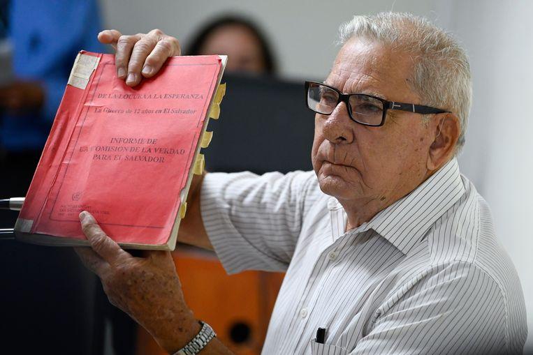 Voormalig legergeneraal Juan Rafael Bustillo toont in de rechtbank een map met documenten gedurende zijn verhoor over de slachting in El Mozote. Beeld AP