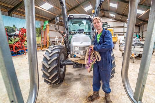 Dirk Gravesteyn bij zijn tractor, van levensbelang voor zijn bedrijf.