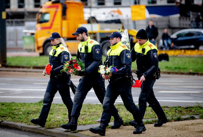 Politiemensen verplaatsten vanochtend bloemen naar een verkeersveiliger plek op het 24 Oktoberplein, de dag na de aanslag waarbij drie mensen om het leven kwamen.