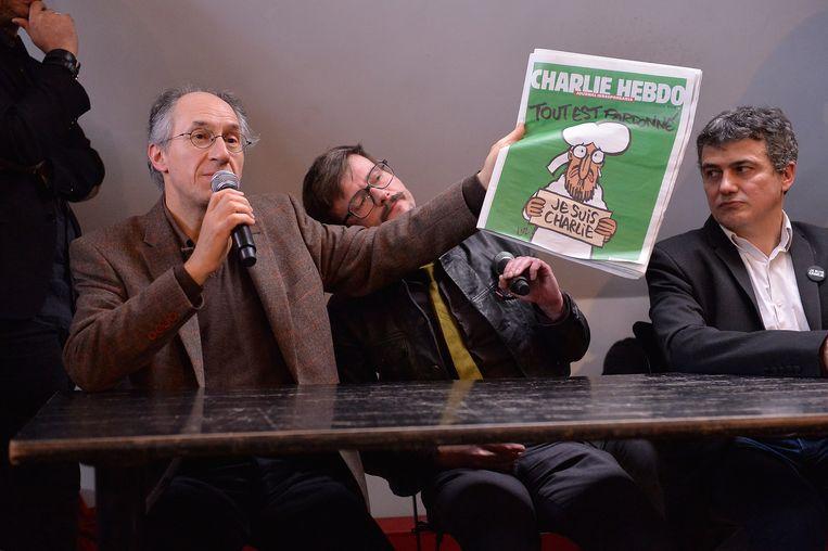 De redactie van Charlie Hebdo presenteert het nieuwe nummer. Beeld getty