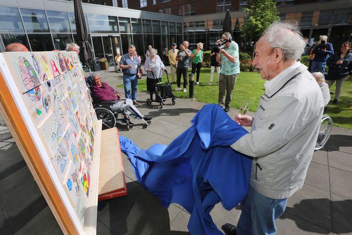 Steef Muller (91) onthult het kunstwerk dat senioren samen met Surplus hebben gemaakt ten tijde van corona. Op de achtergrond (in het groene shirt) Paula Ackermann.