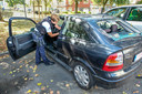 De agentes controleren een voertuig met ingeslagen ruiten.