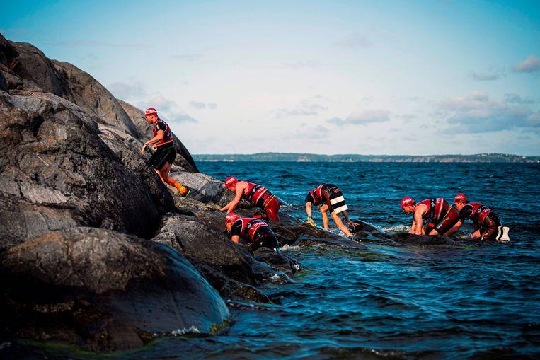320 Atleten uit 25 landen doen mee aan de Otillo Swimrun Race in de archipel van de Zweedse hoofdstad Stockholm. De sporters werken in duo's en zijn met een touw aan elkaar verbonden. Zo rennen en zwemmen ze naar de finish.  Beeld AFP