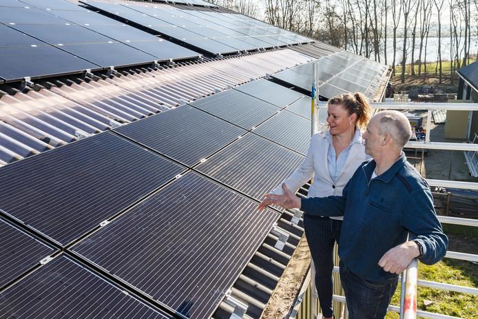 Voorzitter Johan en Roeland en bestuurslid Marieke de Boer bekijken de al geplaatste zonnepanelen op het dak van het Hippisch Centrum in Genemuiden.