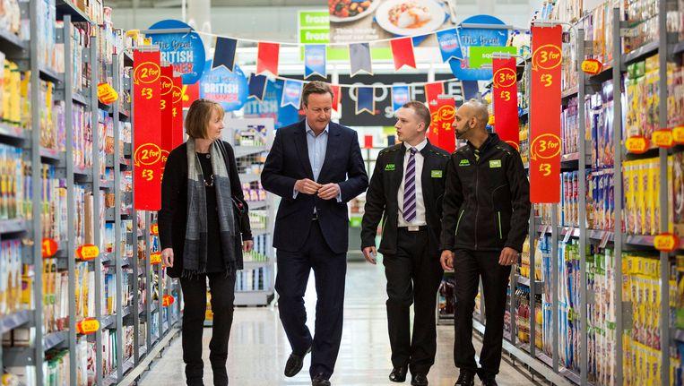 David Cameron en Harriet Harman praten in een ASDA-supermarkt met twee werknemers. Beeld reuters