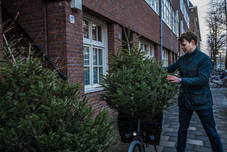 Frederik Kampman doet alsof hij kerstbomen aan het verzamelen is in de Rivierenbuurt, Amsterdam. Lowlander Beer maakt er bier van. Toen zij begonnen zijn is hij wel met een fiets rondgereden maar nu doen ze het gewoon met een bus. Beeld Waldthausen Marlena