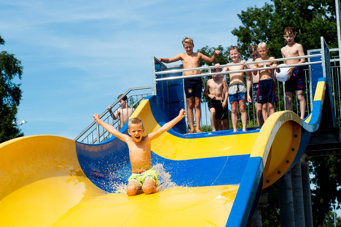 Bram de Vos is de 40.000e bezoeker van Zwembad de Welters dit seizoen. In volle vaart glijdt hij van de glijbaan.