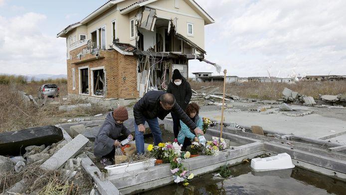 Nabestaanden leggen bloemen voor de slachtoffers van aardbeving en tsunami.