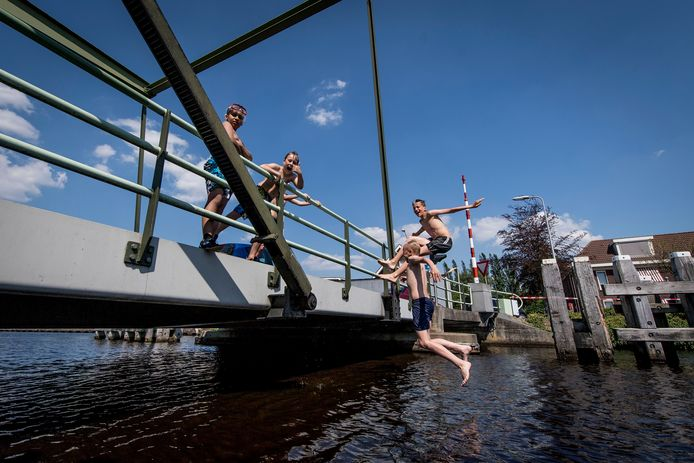 Kinderen springen van de brug over het kanaal in Daarlerveen om wat verkoeling te zoeken.