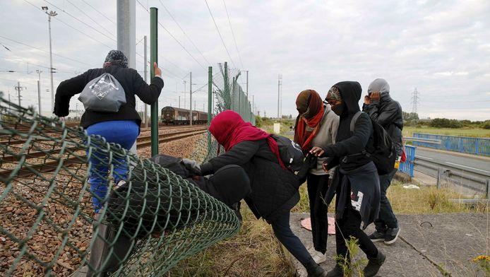 Vluchtelingen klimmen in Calais over een hek om de spoortunnel van de Kanaaltunnel te bereiken.