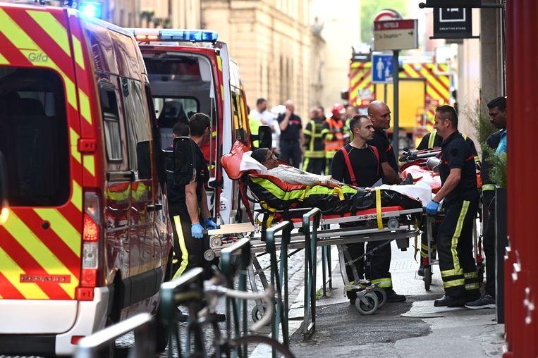 Ambulanciers brengen een gewond slachtoffer weg.