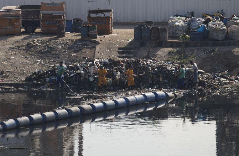 Braziliaanse arbeiders halen drijvend vuil uit het water. Beeld ap