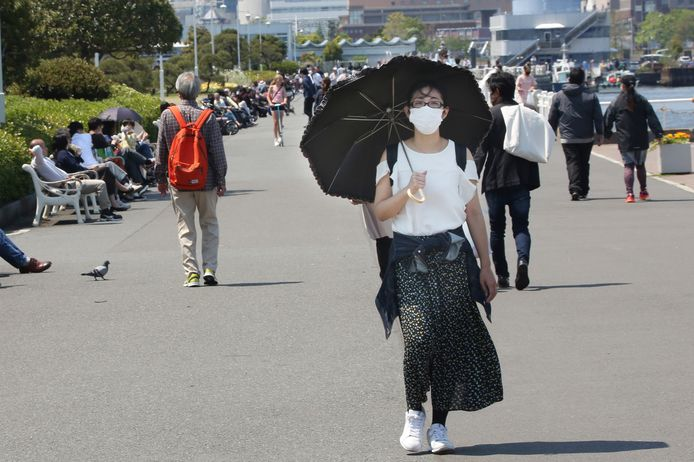 Een Japanse vrouw wandelt door een park in Yokohama, vlakbij Tokio, terwijl Japan worstelt met een tweede golf besmettingen.
