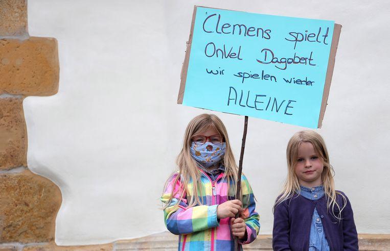 Twee kinderen met het bord 'Clemens speelt Oom Dagobert, wij spelen weer alleen' bij de Tönnies-fabriek.  Beeld EPA
