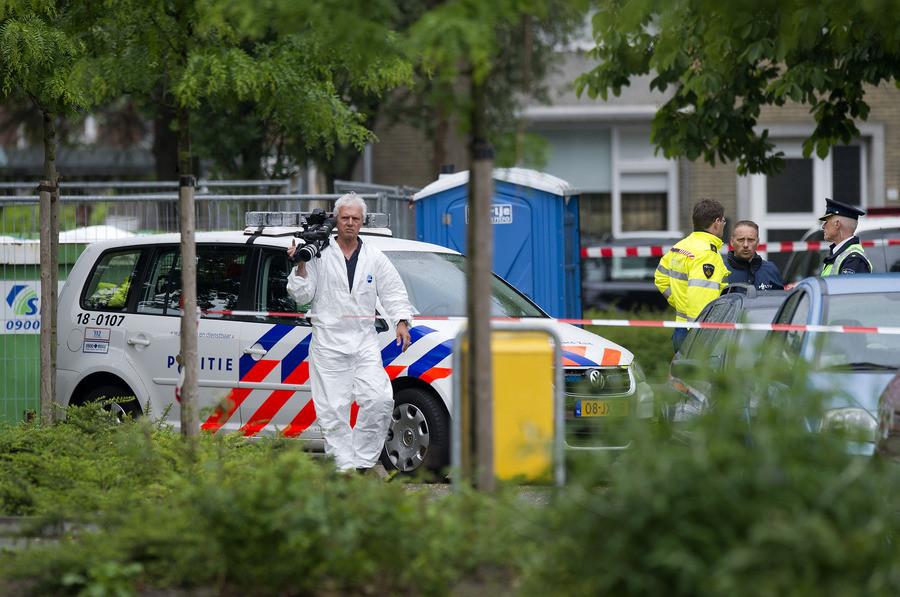 Politiemensen doen onderzoek bij een woning in Zwijndrecht waar bij een schietpartij drie mensen om het leven zijn gekomen.©ANP