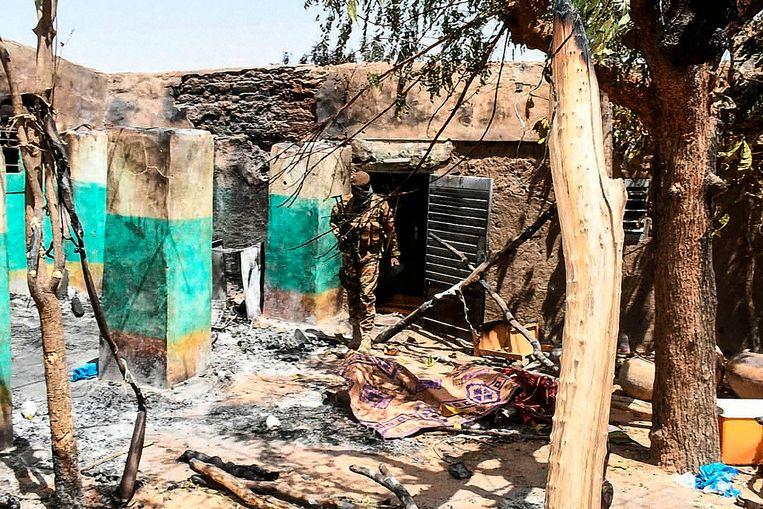 Een soldaat loopt tussen het puin van een verwoest huis tijdens een aanval op 23 maart, in het dorp Ogossagou, in de buurt van Mopti.  Beeld AFP