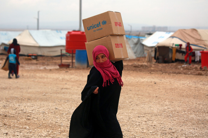 Een Syrische vrouw met een VN-hulppakket, februari 2018. Dit specifieke kamp wordt niet genoemd in de onderzoeken.