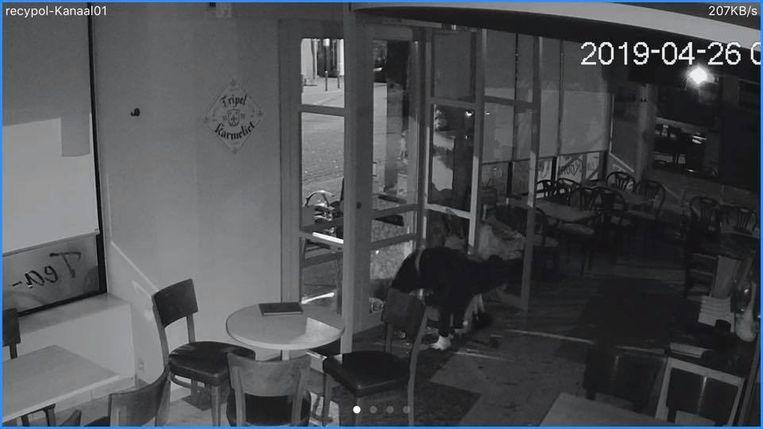 Eén van de daders kruipt door het gat in de toegangsdeur van tearoom 't Kapoentje.