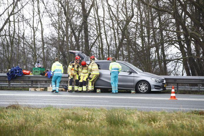 De hulpdiensten zijn aanwezig bij de gecrashte auto.