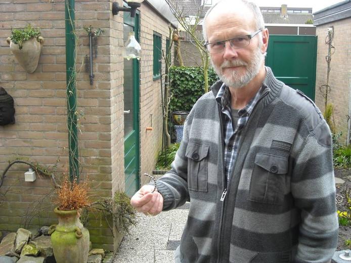 Chris Duijvestijn met het kleine armbandje tussen duim en vingers. De vraag of het sierraad Keltisch is, wil de Stadsarcheoloog graag beantwoord zien.foto Harry Veenstra